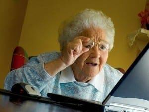 old lady adjusting glasses computer
